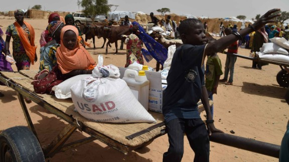 Displaced people fleeing from Boko Haram incursions into Niger attend a World Food Programme (WFP) and USAID food distribution at the Asanga refugee camp near Diffa on June 16, 2016.