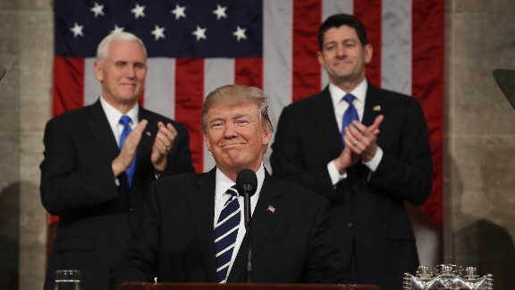 Vice President Mike Pence (L) and Speaker of the House Paul Ryan (R) applaud as President Donald J. Trump (C) arrives to deliver his first address to a joint session of the U.S. Congress on February 28, 2017.