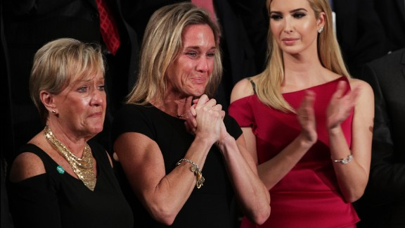 "Carryn Owens, center, cries as she is applauded by the chamber during Trump's speech. Owens' husband, Navy SEAL William ""Ryan"" Owens, recently was killed during a mission in Yemen. ""Ryan died as he lived: a warrior and a hero, battling against terrorism and securing our nation,"" Trump said. The applause lasted over a minute, which Trump said must be a record."