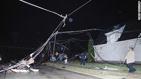People walk past downed wires after a storm moved through Naplate, Illinois, on Tuesday.