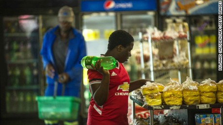 A woman holds a bottle of soft drink at a local supermarket in Greater Johannesburg.