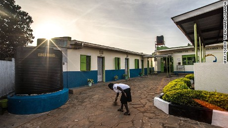 A RHU staff member sweeps the clinic's courtyard in the early morning before the first patients arrive.