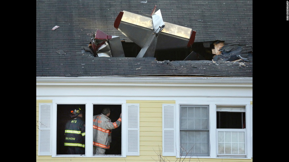Firefighters investigate a condominium building where a single-engine aircraft crashed in Methuen, Massachusetts, on Tuesday, February 28. The pilot was killed. No one in the building was hurt.