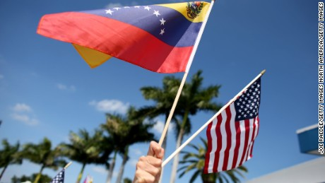 MIAMI, FL - MARCH 01:  A protester holds a Venezuelan and American flag as she and other Venezuelans and their supporters show their support for the anti-government protests in Venezuela on March 1, 2014 in Miami, Florida. In Venezuela, protests over the past couple of weeks have resulted in violence as government opponents and supporters have faced off in the streets.  (Photo by Joe Raedle/Getty Images)