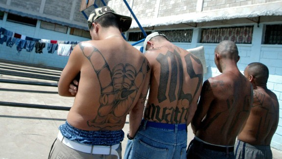 "Tegucigalpa, HONDURAS:  Four unidentified members of the Mara Salvatrucha ""MS-13"" (juvenile gang) show their tatoos in the unit where they are kept imprisioned in the National Penitentiary in Tamara, 30km north of Tegucigalpa, 01 February 2006. AFP PHOTO/Elmer MARTINEZ  (Photo credit should read ELMER MARTINEZ/AFP/Getty Images)"