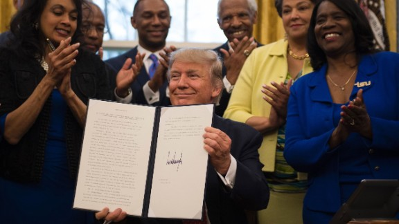 President Donald Trump holds up an executive order to bolster historically black colleges and universities (HBCUs) in the Oval Office of the White House on February 28, 2017.