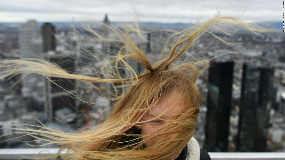 A visitor's hair is ruffled by the wind as stormy weather hits the Main Tower skyscraper in Frankfurt, Germany, on Wednesday, February 22.