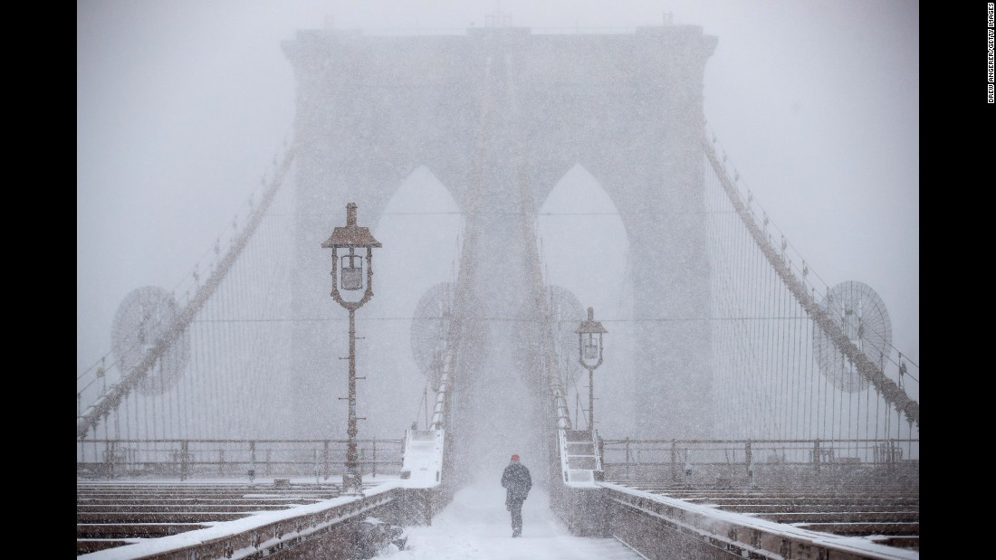 A man walks across the Brooklyn Bridge during a snowstorm in New York on Thursday, February 9.