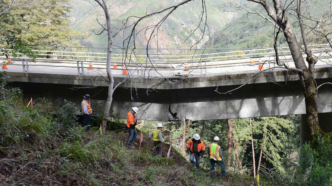 Engineers inspect a crack Wednesday, February 22, at the sagging Pfieffer Canyon Bridge in Big Sur, California. The bridge was damaged in a storm.