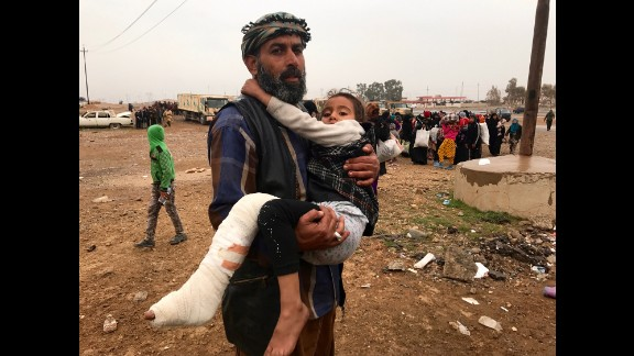 An Iraqi man carries his daughter, wounded by a mortar round that slammed into their home in the Ma