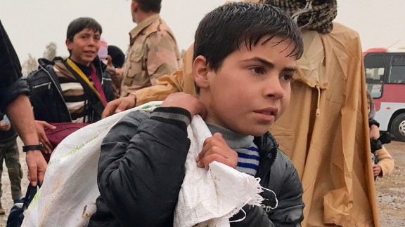 A young Iraqi boy carries a bag on his back as he walks in the rain to a civilian processing station south of Mosul. Some civilians have made the dangerous escape on foot from western Mosul.