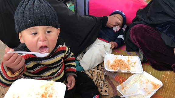 An Iraqi child eats his first hot meal in 10 days at an Iraqi military reception point for internally displaced people south of Mosul.