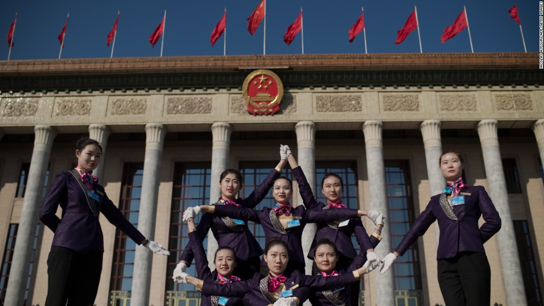 Hostesses pose for a picture in front of the Great Hall of the People.