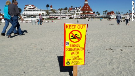 In this March 1, 2017 image, a sign warns of sewage contaminated ocean waters on a beach in front of the iconic Hotel del Coronado in Coronado, Calif. For more than two weeks last month, a stench of feces, ammonium and laundry detergent wafted through the air along Southern California beaches closest to the border. Sewer repair work in nearby Tijuana, Mexico, caused an estimated 143 million gallons to spill into the United States and the Pacific Ocean for 18 days. A Mexican official challenged those findings on Friday after a week of public uproar. (AP Photo/Gregory Bull)