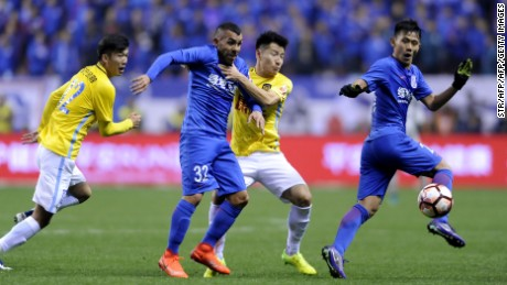 Shanghai Shenhua's Argentine striker Carlos Tevez (2L) fights for the ball with Yang Xiaotian (2R) of Jiangsu Suning during their Chinese Super League football match in Shanghai on March 5, 2017. / AFP PHOTO / STR / CHINA OUT        (Photo credit should read STR/AFP/Getty Images)