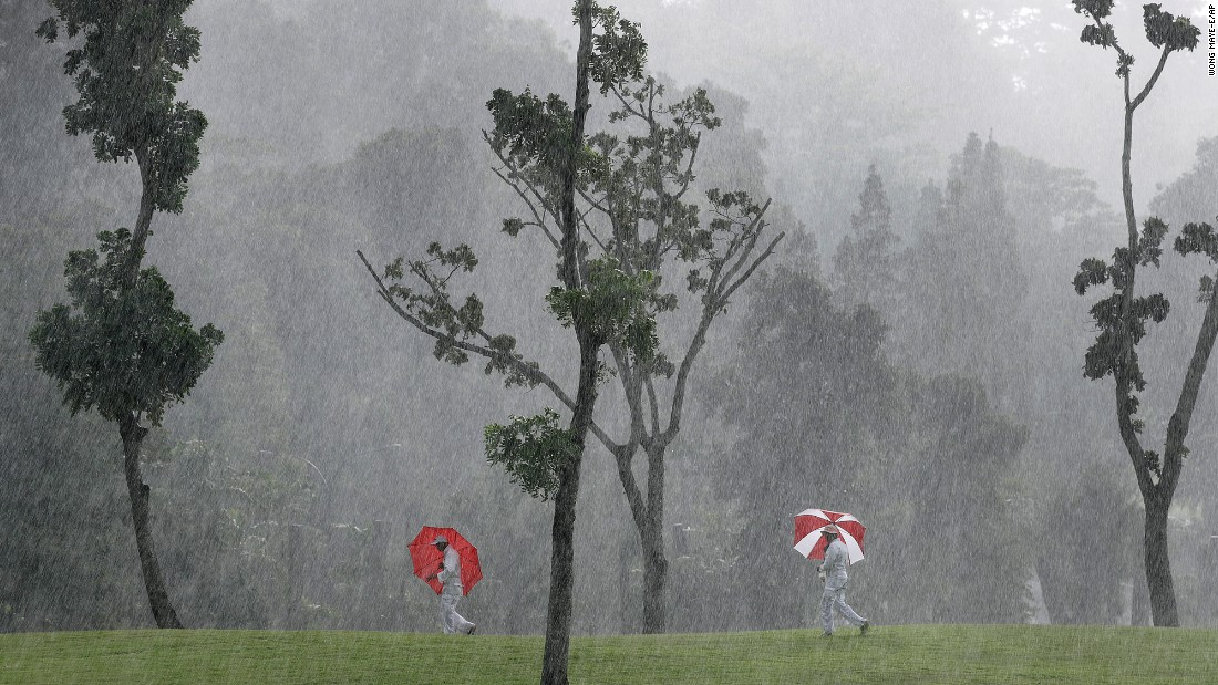 Course marshals carry umbrellas at an LPGA event in Singapore on Friday, March 3.