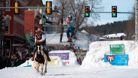 TOPSHOT - Rider Jeff Dahl races down Harrison Avenue while skier and son Greg Dahl airs out off the final jump of the Leadville skijoring course during the 68th annual Leadville Ski Joring weekend competition on Saturday, March 4, 2017 in Leadville, Colorado. 