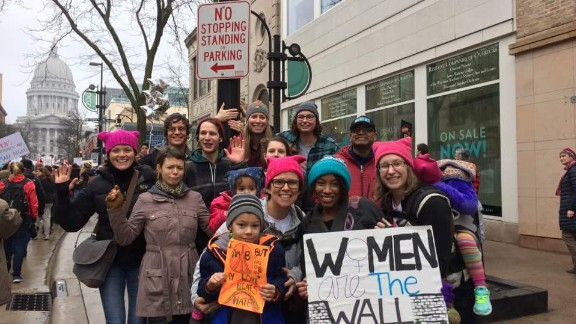 """Charisse Daniels, in the teal hat, holds a sign saying, """"Women are the wall and Trump will pay."""""""