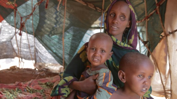Fatuma Hassan Hussein sits with her two children Shankaron, 3, and Rahma, 15 months, in a makeshift shelter in Baidoa, Somalia. Fatuma says she was having trouble feeding her family. She says she traveled more than a hundred miles to get to the camp.