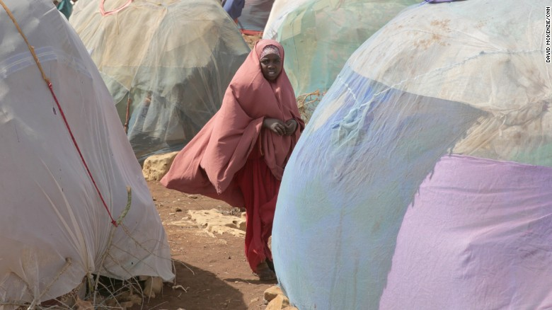 A young girl stands in front of makeshift shelters in Baidoa. More than 6 million people need food assistance in Somalia.