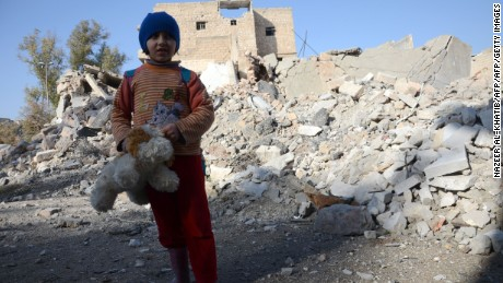 A Syrian girl, holding her stuffed toy, stands next to the rubble of buildings last month in the northwestern Syrian border town of al-Bab.