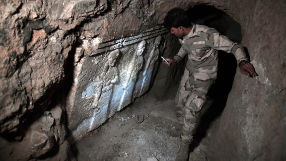 A member of the Iraqi troops examine ancient artifacts found in an underground ISIS tunnel in eastern Mosul.