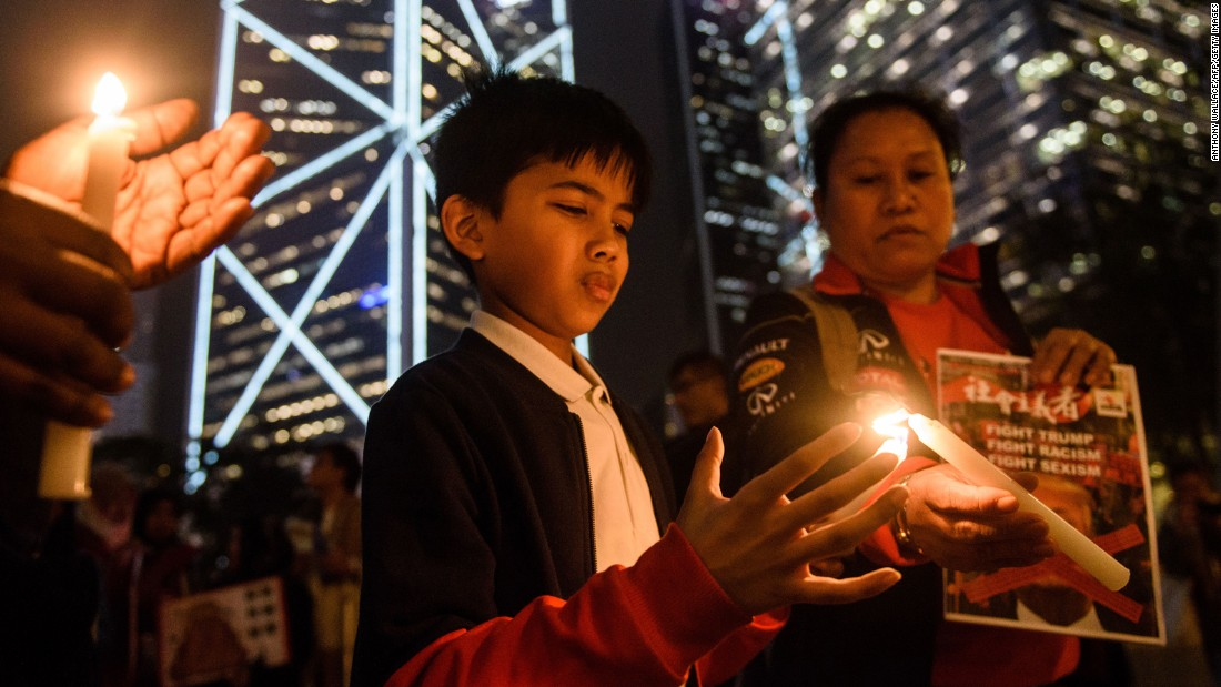 A woman helps a boy light a candle in Hong Kong.