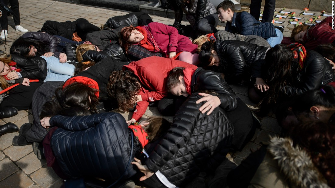 People in Bucharest, Romania, lie on the ground during a performance to raise awareness about women killed by their partners.