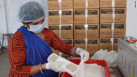 A worker loads boxes with Saathi banana fiber sanitary pads. Saathi produces about 1,300 pads a day.