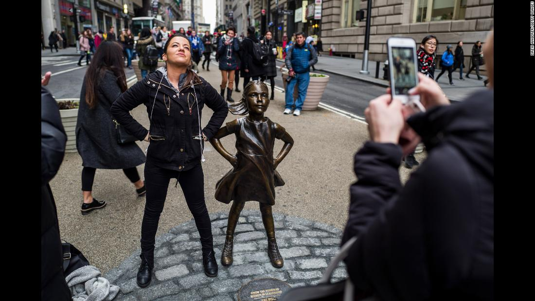 "A woman mimics the defiant stance of the ""Fearless Girl."""