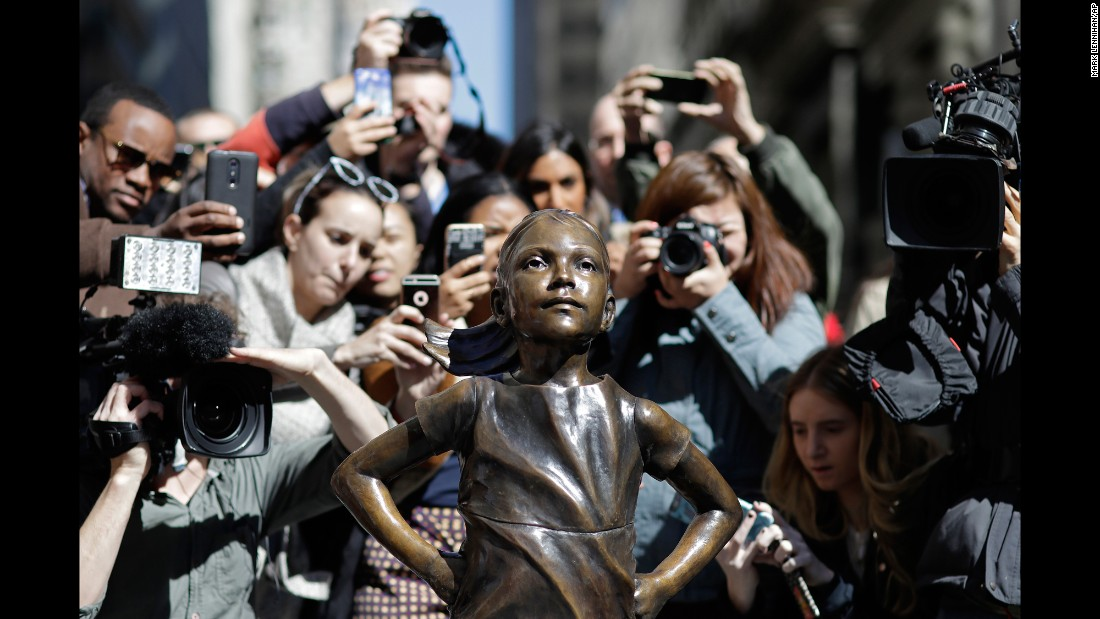 "People stop to photograph the ""Fearless Girl"" statue facing Wall Street's charging bull sculpture Wednesday, March 8, in New York. State Street Global Advisors installed <a href=""http://www.cnn.com/2017/03/09/us/gallery/fearless-girl-wall-street/index.html"" target=""_blank"">the statue</a> ahead of <a href=""http://www.cnn.com/2017/03/08/world/gallery/international-womens-day-marches-2017/index.html"" target=""_blank"">International Women's Day.</a> The asset manager designed it to call attention to its new initiative to increase the number of women on its clients' corporate boards."