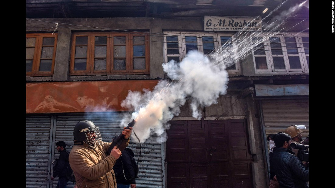 A police officer fires tear gas at Kashmiri protesters during an anti-India protest in Srinagar, India, on Friday, March 3.