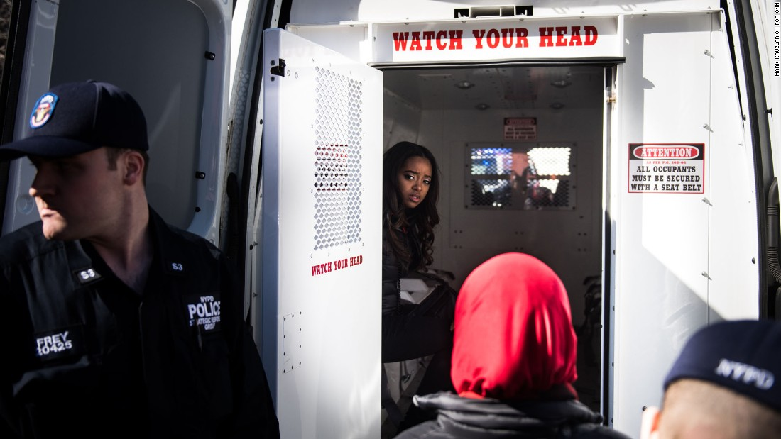 "Activist Tamika Mallory, one of the founders of the Women's March movement, sits in the back of a police van Wednesday, March 8, after being detained for blocking traffic outside the Trump International Hotel and Tower in New York. Thirteen women outside the hotel <a href=""http://www.cnn.com/2017/03/08/politics/womens-march-organizers-detained/"" target=""_blank"">were arrested for disorderly conduct</a> during the ""Day Without a Woman"" march, a spokesman for the New York Police Department said. <a href=""https://twitter.com/womensmarch/status/839558787753263104"" target=""_blank"">The Women's March tweeted:</a> ""Many of our national organizers have been arrested in an act of civil disobedience. We will not be silent."""