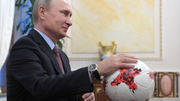 """Russian President Vladimir Putin places his hand on an official match ball for the 2017 FIFA Confederations Cup, named """"Krasava"""""""