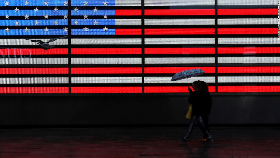 A person walks by a digital American flag at New York's Times Square on Tuesday, March 7.