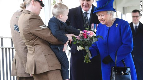 LONDON, ENGLAND - MARCH 9:  Alfie Lun, 2, is held up by his mother Michelle as he hands a bouquet to Queen Elizabeth II during the unveiling of the new memorial to members of the armed services who served and died in the wars in Iraq and Afghanistan at Victoria Embankment Gardens on March 8, 2017 in London, England. (Photo by Toby Melville - WPA Pool/Getty Images)