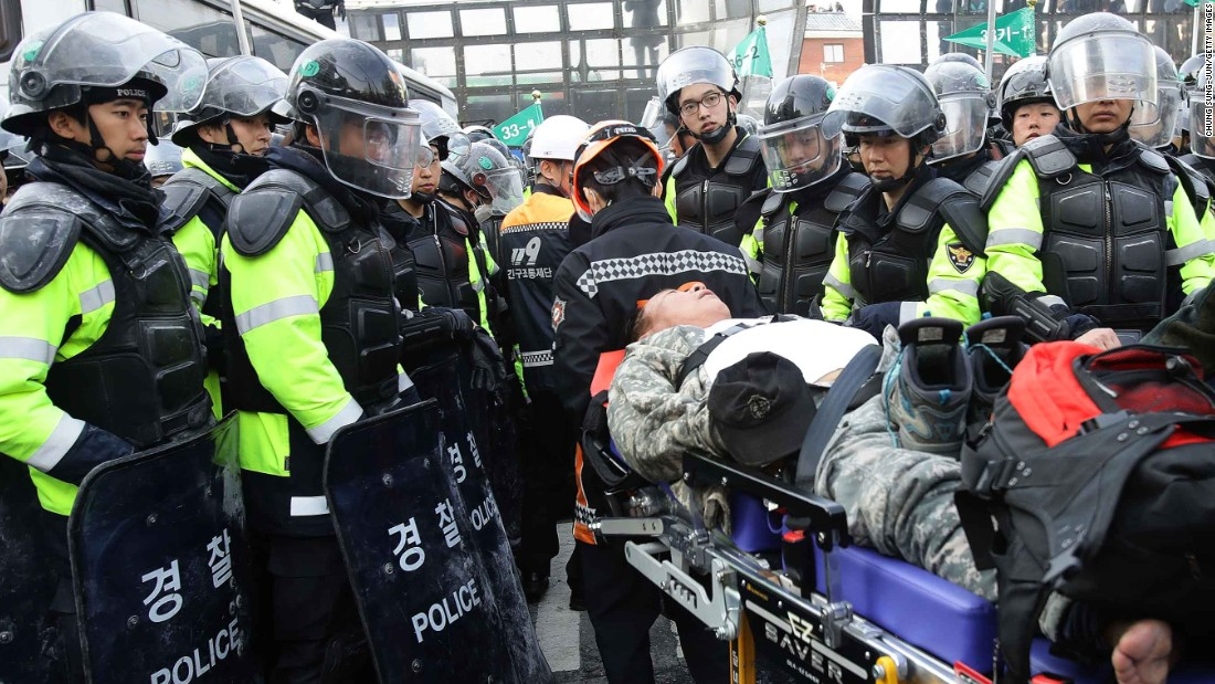 An injured Park supporter lies on a stretcher surrounded by police.