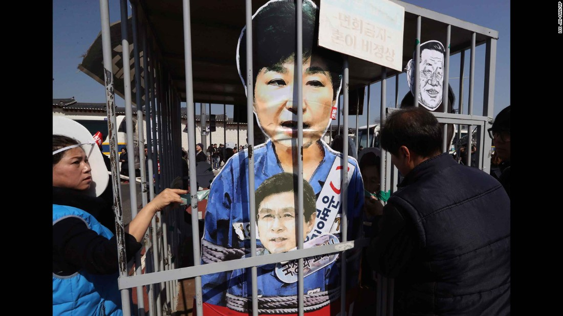 Protesters view cutouts of Park and Hwang during a march toward the Blue House.