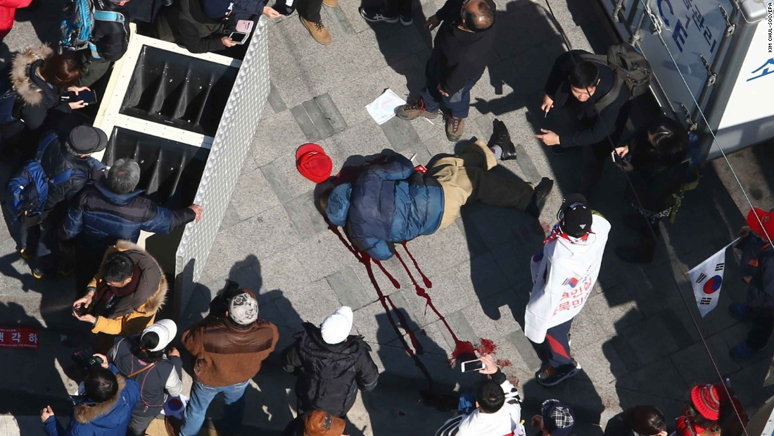 A supporter of the ousted president lies in a pool of blood as protesters push to pass a police barricade preventing them from reaching the Constitutional Court. According to police, two people died in the protests. A statement from acting President Hwang Kyo-ahn said several people also were injured.