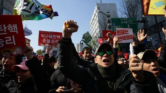 South Koreans celebrate after hearing the Constitutional Court
