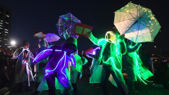 Demonstrators wearing illuminated costumes take part in a rally demanding Park's arrest. Now stripped of her immunity, Park is vulnerable to prosecution in the scandal that triggered her removal. Lawmakers and judges agreed that she abused her authority in helping a friend raise donations from companies.