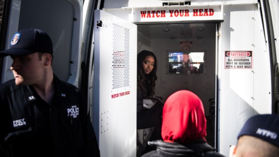 """Activist Tamika Mallory, one of the founders of the Women's March movement, sits in the back of a police van Wednesday, March 8, after being detained for blocking traffic outside the Trump International Hotel and Tower in New York. Thirteen women outside the hotel <a href=""""http://www.cnn.com/2017/03/08/politics/womens-march-organizers-detained/"""" target=""""_blank"""">were arrested for disorderly conduct</a> during the """"Day Without a Woman"""" march, a spokesman for the New York Police Department said. <a href=""""https://twitter.com/womensmarch/status/839558787753263104"""" target=""""_blank"""" target=""""_blank"""">The Women's March tweeted:</a> """"Many of our national organizers have been arrested in an act of civil disobedience. We will not be silent."""""""