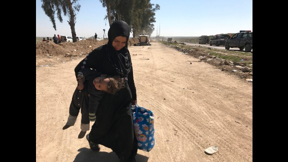 A woman carries her child in one hand and a bag of belongings in the other as she flees western Mosul
