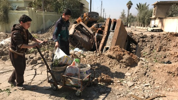 Two Iraqi teenagers in western Mosul throw trash into a crater made by a coalition airstrike on ISIS positions.