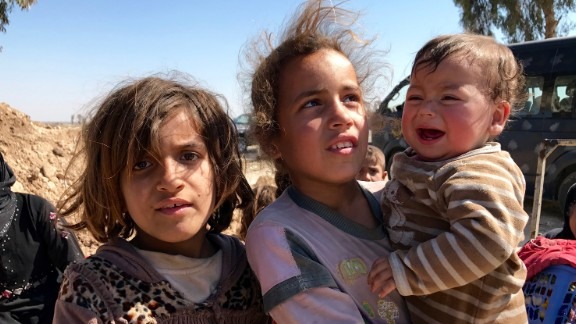 Two girls hold their little brother as they wait for Iraqi security forces to transfer them to a nearby refugee camp.