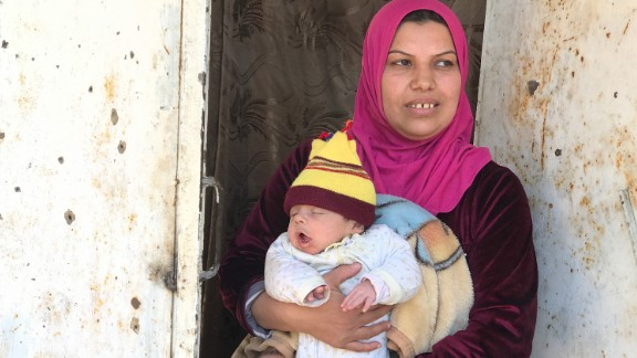 Um Mohammed, one of the few civilians remaining in western Mosul as fighting rages, stands in front of her house holding her month-old son. She told CNN that her family hid with several others in the basement of her house for 16 days while the battle raged. They lived on cold porridge because there was no running water or electricity in the city. Um Mohammed said she had to give the children sleeping medicine so ISIS wouldn
