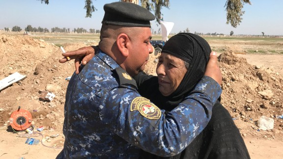 An Iraqi Federal Police officer hugs and kisses the forehead of a woman named Mariam who fled with her family from the Mahata neighborhood early in the morning. Mariam told CNN that ISIS forbade her to smoke, yet their fighters drank alcohol, smoked and took pills. She said anyone caught smoking under ISIS rule was punished, sometimes by having their tongues or fingers cut off.