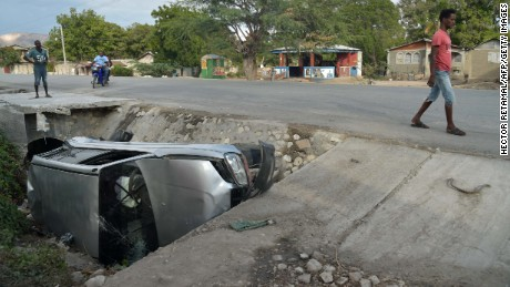 A car damaged by a bus lies on the side of a road on March 12, 2017 in Gonaives, 150 km (90 miles) northwest of the capital Port-au-Prince. A bus speeding away from a hit-and-run accident plowed into dozens of street musicians in northern Haiti, killing 34 people, officials said.  / AFP PHOTO / HECTOR RETAMAL        (Photo credit should read HECTOR RETAMAL/AFP/Getty Images)