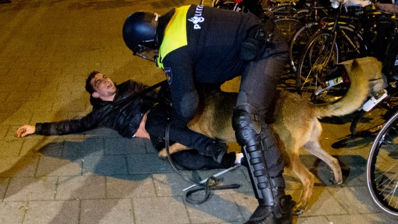 A Dutch riot police officer tries to get his dog to let go of a man after riots broke out during a demonstration at the Turkish consulate in Rotterdam, Netherlands, on Sunday, March 12.