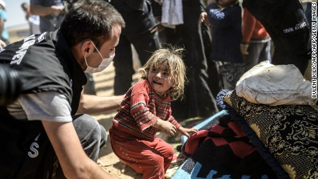 A Syrian Kurdish child cries as Turkish police search their bags after they crossed the border between Syria and Turkey at the southeastern town of Suruc in Sanliurfa province on September 23, 2014.